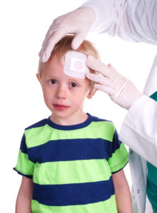 little boy in green and blue striped shirt with a head injury getting a bandage while facing the camera