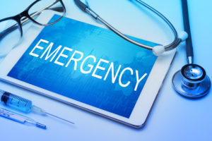Emergency word on tablet screen with medical equipment typically found in an urgent care
