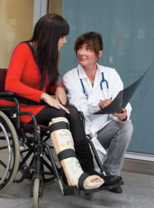 Young woman with leg in plaster. Talking to a doctor